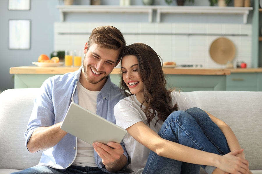 Insurance Quote - Young Couple Sitting On Couch In Apartment Using Tablet